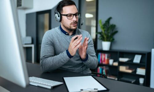 Young handsome male customer support phone operator with headset working in his office.